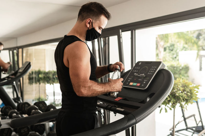 Man wearing mask holding water bottle while standing on treadmill