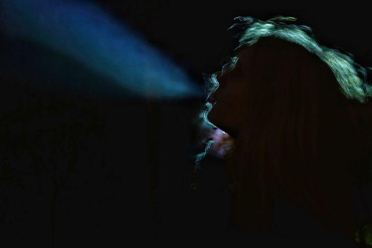 Teenage girl smoking cigarette in dark