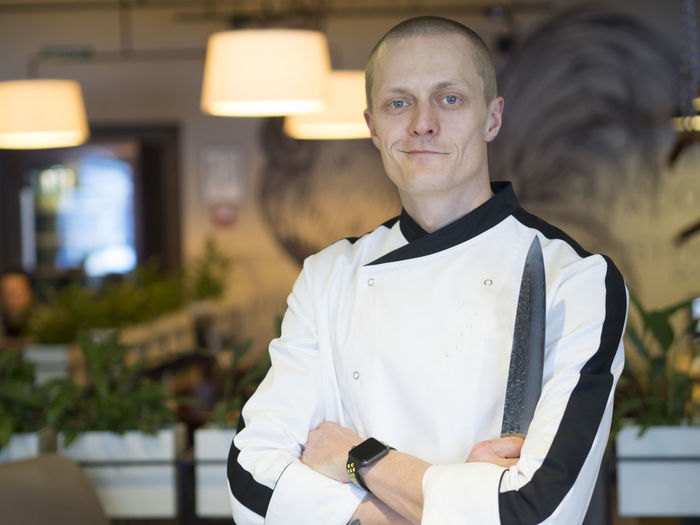 Portrait of confident chef with arms crossed standing at restaurant