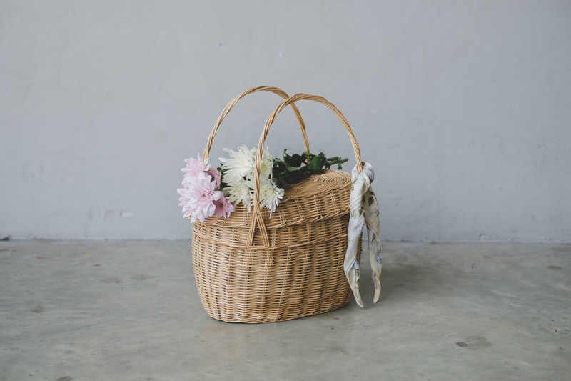 Flowers On Basket Over Floor Against Wall