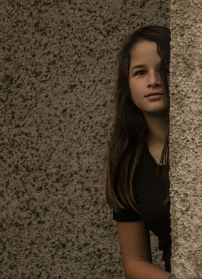 Portrait of girl hiding behind wall