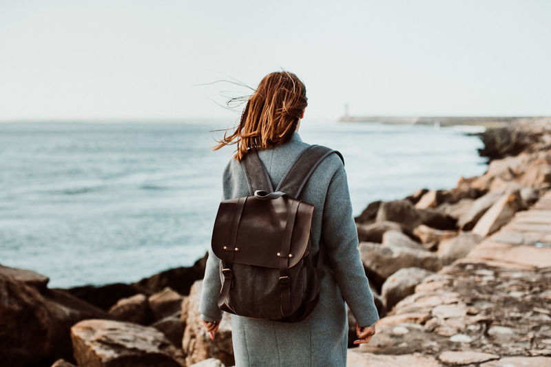 Rear view of woman wearing backpack while standing on pier over sea against clear sky