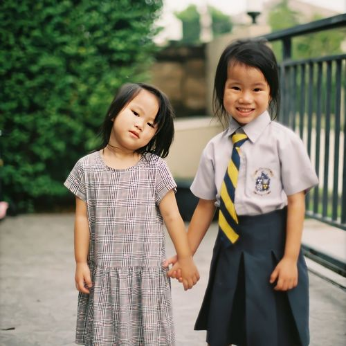 Portrait of girl wearing school uniform standing with sister