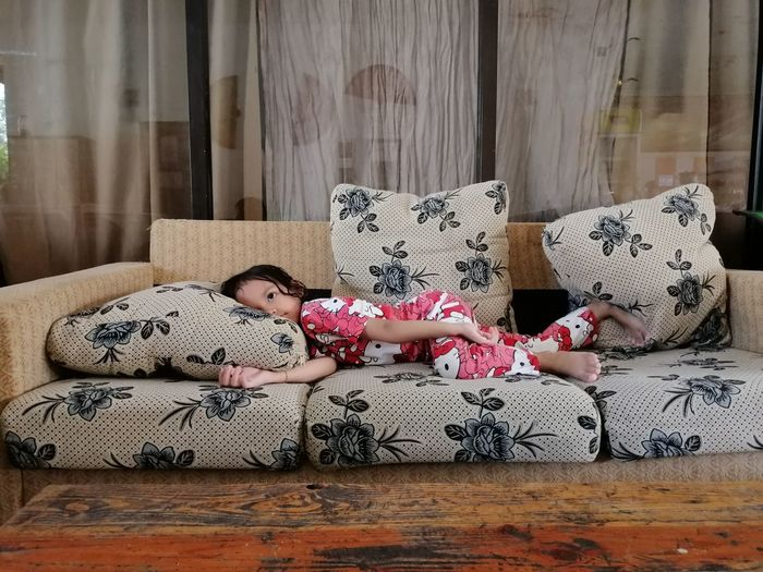 Side view of girl lying on sofa at home