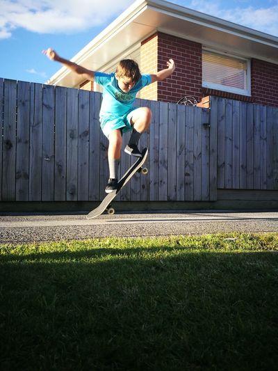 Full length of boy skateboarding on street during sunny day