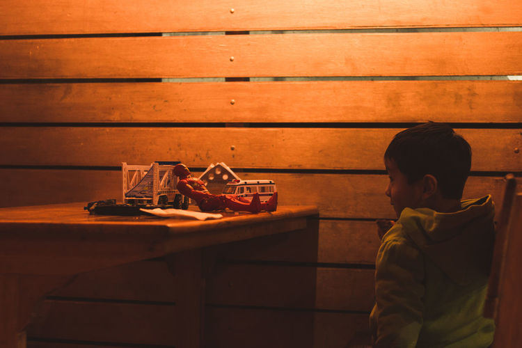 Boy sitting by toys on wooden table