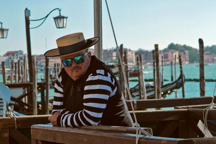 Portrait of senior man sitting in boat against sky