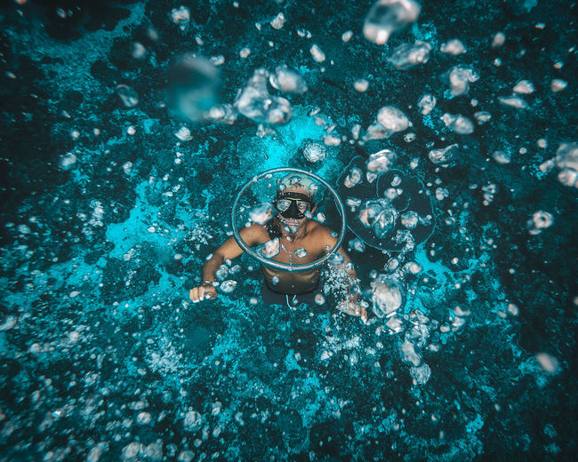 High angle view of man swimming in abyss of the ocean making water rings