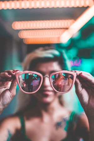 Sunglasses Real People Eyeglasses  Holding One Person Human Hand Focus On Foreground Leisure Activity Reflection Lifestyles Glasses Young Adult Human Body Part Close-up Eyewear Looking At Camera Young Women Day Portrait Technology