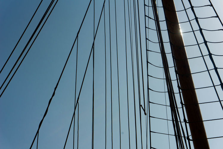 Low angle view of mast against clear sky during sunny day