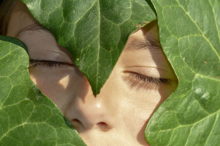 Close-up of girl with leaves and eyes closed