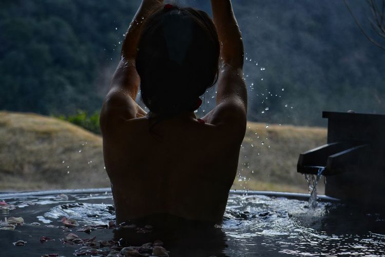 Rear view of shirtless woman in hot spring