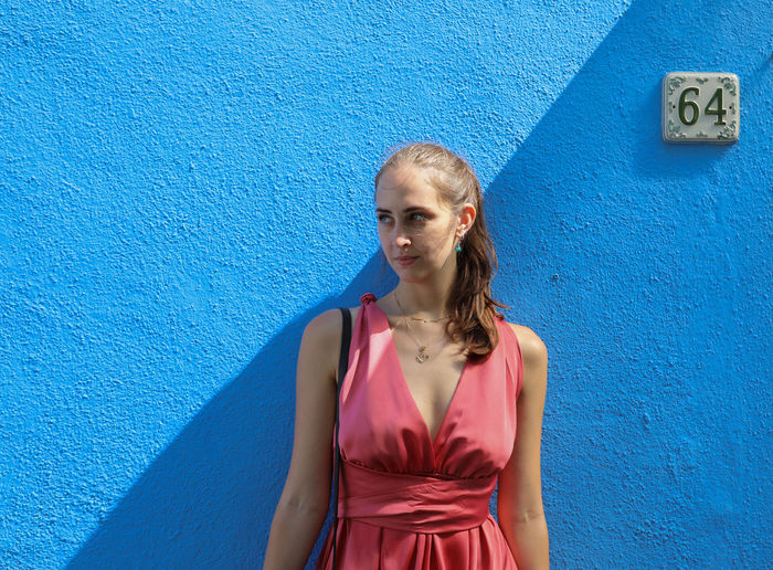 Portrait of young woman standing against blue wall