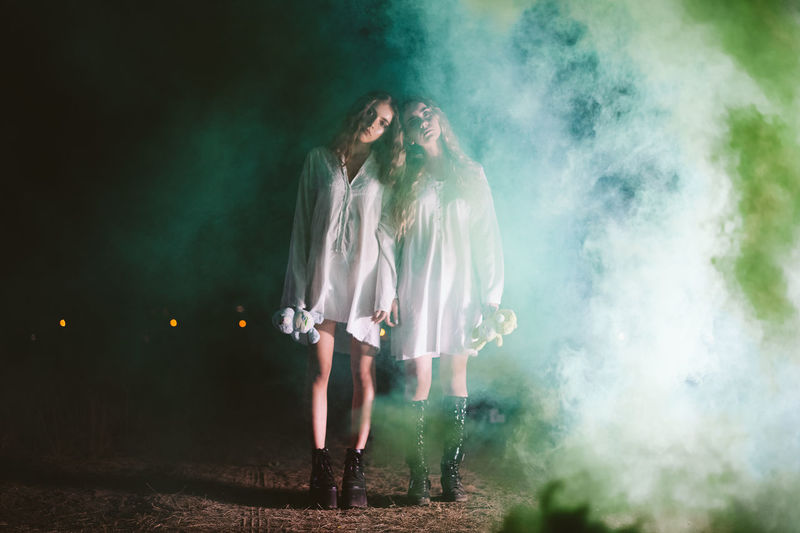 Full length portrait of female friends standing amidst smoke on land at night
