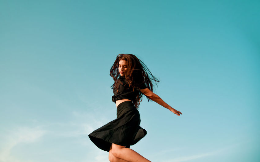 Low angle view of woman jumping against clear blue sky