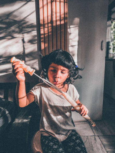 Cute girl holding bubble wand sitting at home