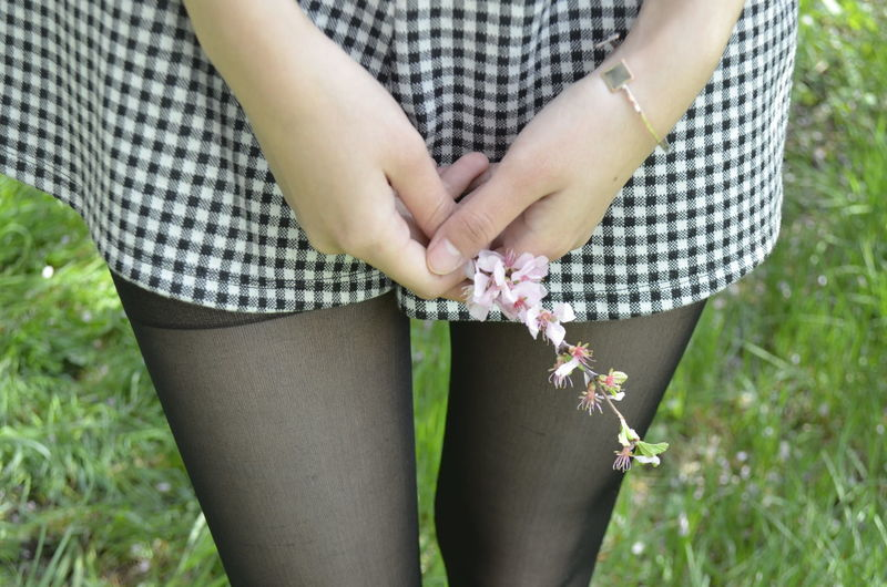 Midsection of woman holding flower