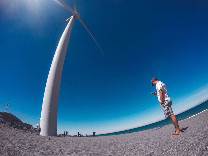 Low angle view of man standing by windmill against clear blue sky
