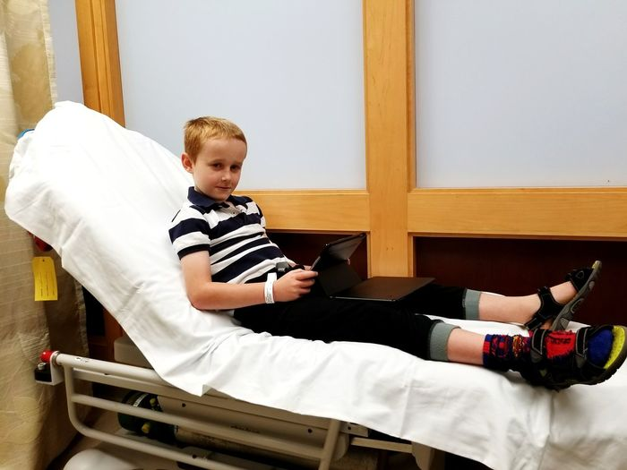 Portrait of boy with digital tablet sitting on bed in hospital