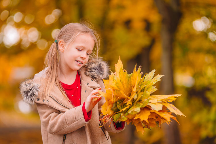 Portrait of smiling girl holding yellow autumn leaf