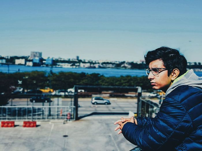 Side View Of Thoughtful Young Man Against Sky In City On Sunny Day