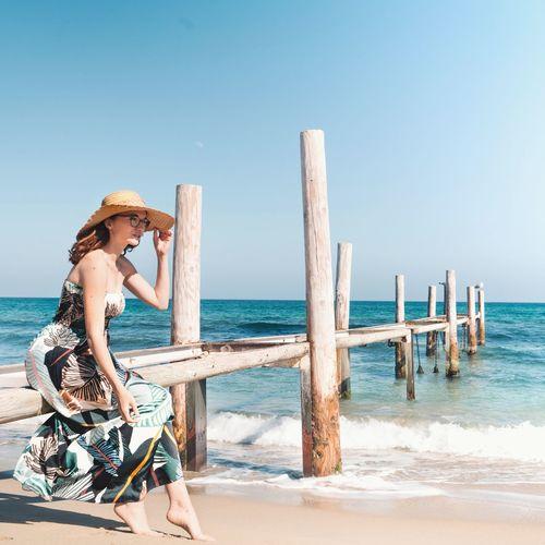 Woman on beach against clear sky
