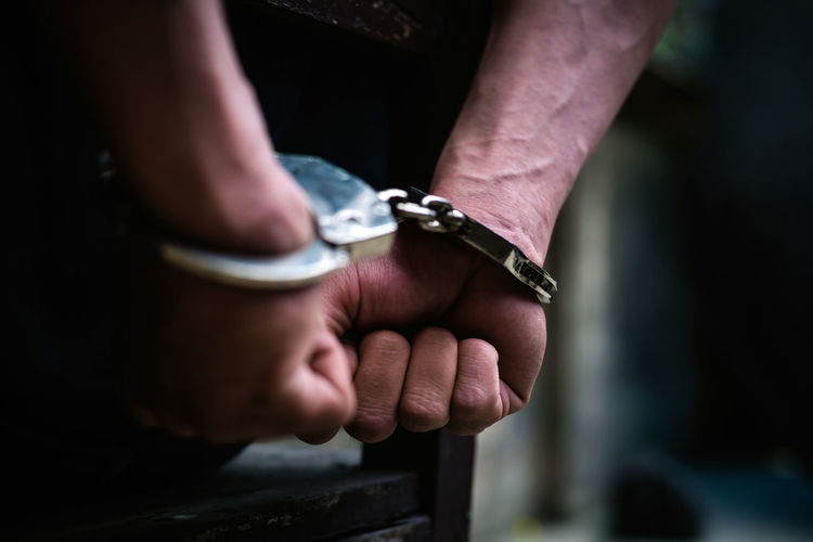 Human Hand Hand Human Body Part Crime One Person Social Issues Men Holding Handcuffs  Close-up Real People Prisoner Selective Focus Punishment Metal Day Midsection Indoors  Aggression  Finger Shackle Escape Freedom Jail Violence