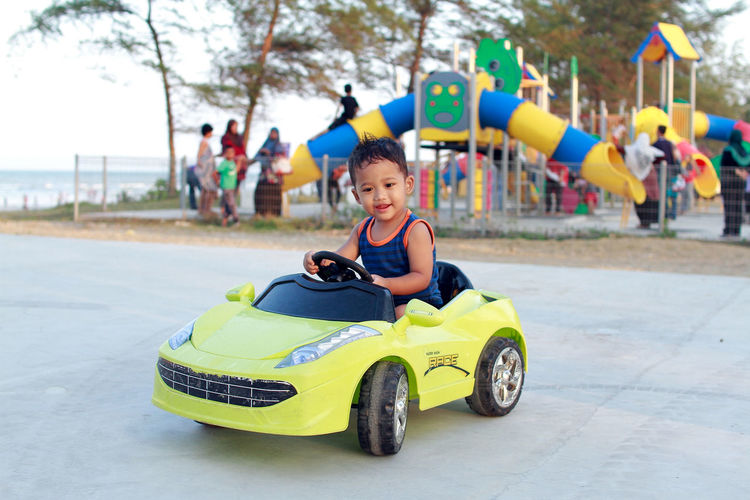 Cute baby boy driving toy car at playground