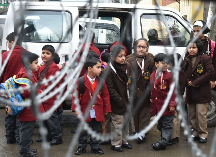 students walk towards the school next to barbed wire on the first day of the schooling session in Srinagar, Kashmir. The schools and colleges re-opened in Kashmir on Monday after nearly three-month-long winter vacation. Kashmir Srinagar Kashmir India School Schoolchildren Vaccation Barbedwire