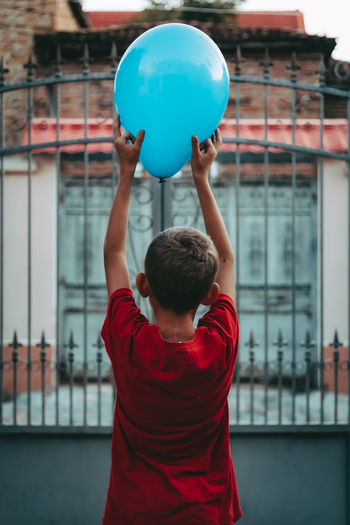 Rear view of man playing with balloons