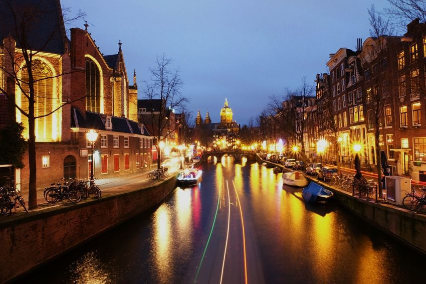 Streets of Amsterdam. Illuminated Dusk Reflection Night Architecture Building Exterior River Built Structure Street Light Sky Travel Destinations City Tree Water Outdoors Cityscape Bridge - Man Made Structure No People FUJIFILM X-T10 Amsterdam Netherlands Travel Photography Arch Tourism Travel