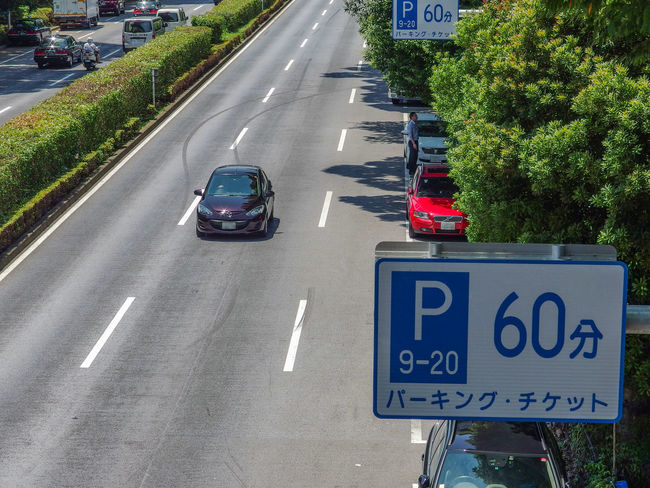 japanese traffic sign board with running car on road Transportation Mode Of Transportation Motor Vehicle Car Road Land Vehicle Communication Text City Sign Symbol Street Western Script Plant Road Marking Marking Day Tree Architecture Direction Guidance No People Outdoors Road Sign