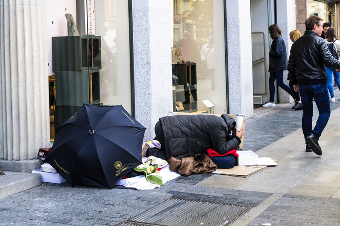 Man begging on the pavement in Gran Via Madrid. Begging City City Life City Street Editorial  Madrid People Social Issues Street Street Living Tourism Travel Umbrella