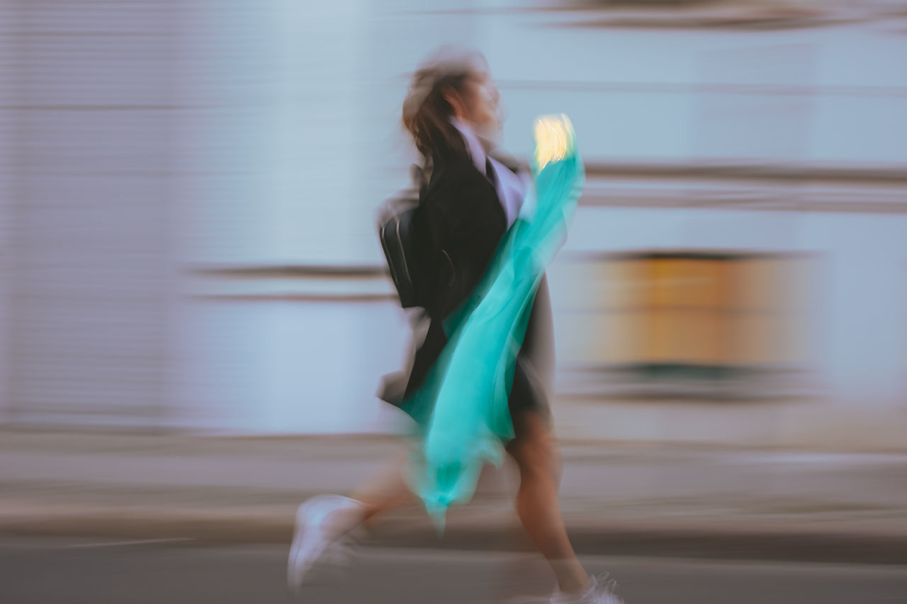 Side view of woman holding illuminated lighting equipment with scarf running on road in city