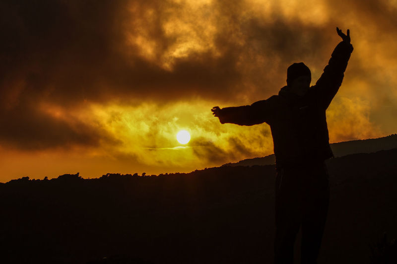 Silhouette Man With Arms Outstretched Standing Against Orange Sky