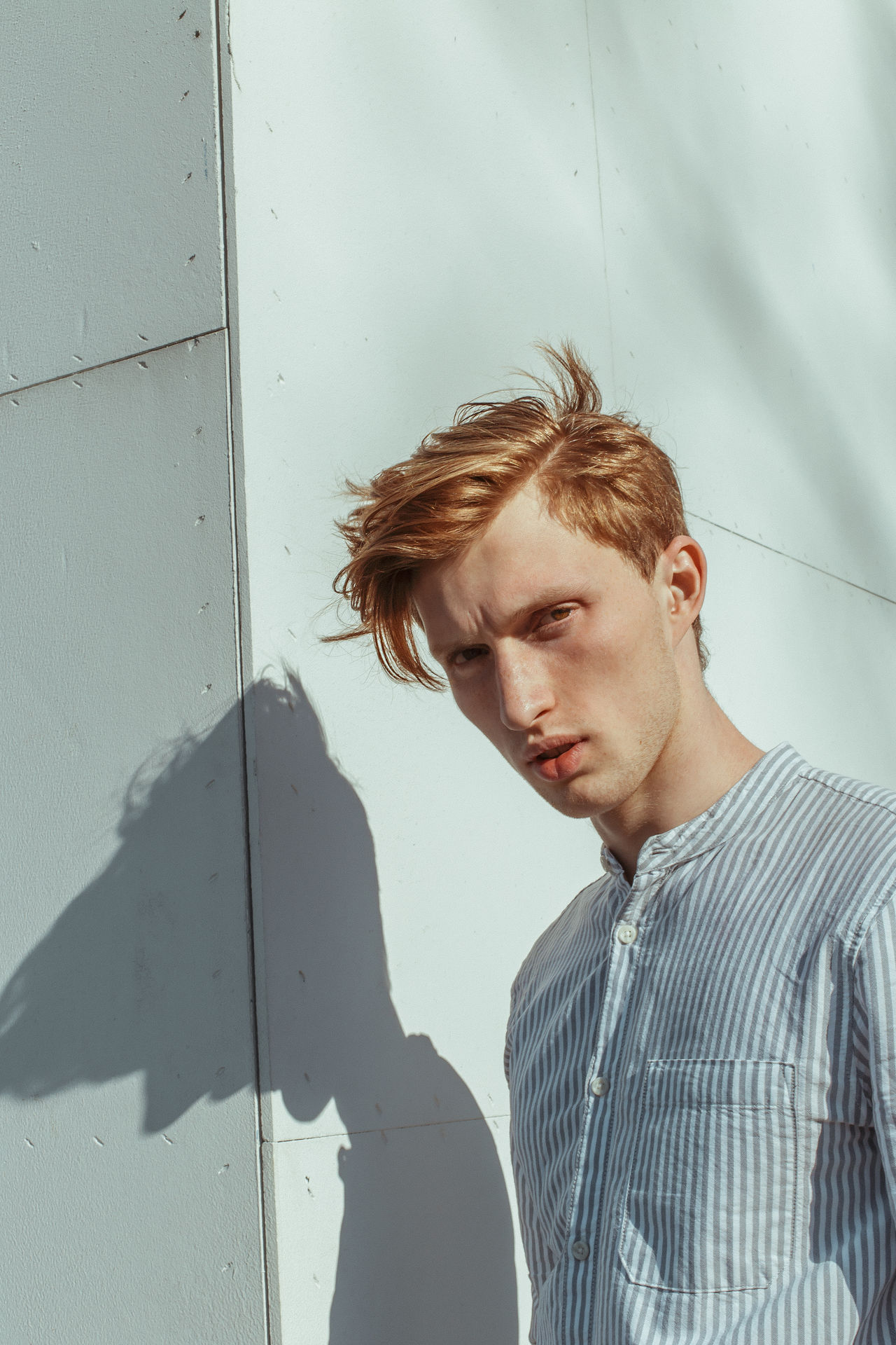 PORTRAIT OF YOUNG MAN LOOKING AWAY WHILE STANDING ON WALL