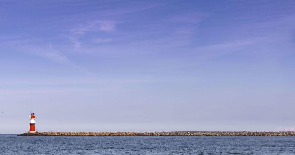 Lighthouse by sea against blue sky