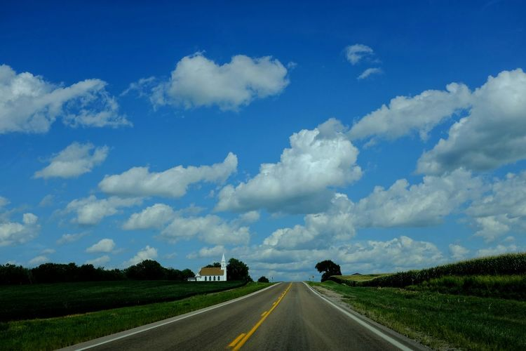 Country Road By Field Against Sky