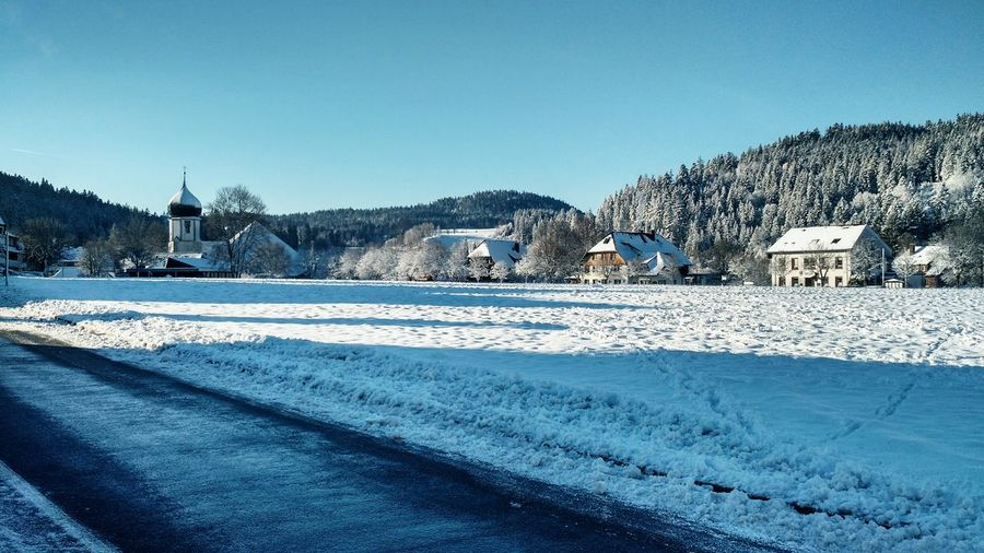 Road by snow covered field against clear sky