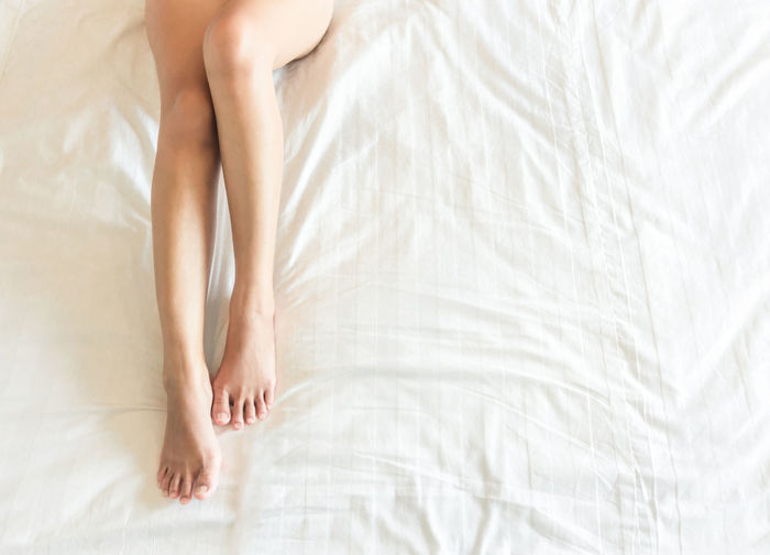 Closeup woman legs with sleeping on white bed, beauty and skin care concept, selective focus Beautiful Bed Foot Shaved Slim Attractive Background Barefoot Beauty Bedroom Body Care Cultivation Depilation Female Girl Healthy Legs Long Lying Down Perfection Relax Seducing Sleep