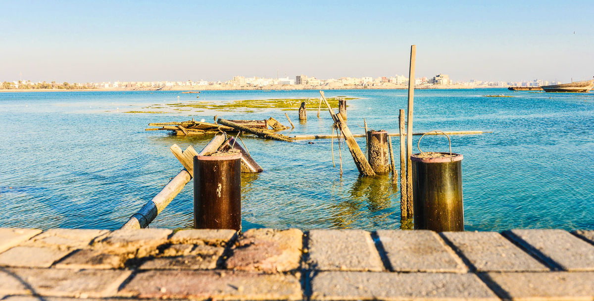 A broken wooden pier in Busaiteen, Bahrain Architecture Beauty In Nature Built Structure Clear Sky Day Nature Nautical Vessel No People Outdoors Post Scenics - Nature Sea Sky Sunlight Tranquil Scene Tranquility Transportation Water Wood - Material Wooden Post