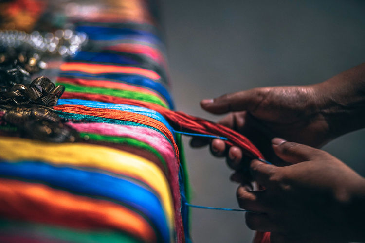 Cropped hands of person holding colorful threads at market stall