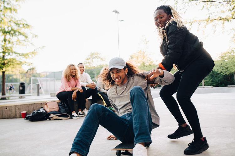 Women sitting on sidewalk in city
