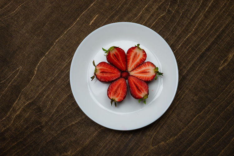 Strawberries on a white plate on a wooden table. creeative background concept. Food And Drink Food Freshness Red Indoors  Still Life No People Strawberry Strawberries Fruit Fruits Fresh Healthy Eating Vehetable Natural Raw Vitamin Raw Food Tasty Breakfast Ripe Juicy Sweet Berry Delicious Nutrition Background Rustic Dessert Freshness Eating Organic Close-up Diet Ingredient Vegan Snack Apperitive Pattern Dark Wooden Table Brown Texture Textured  Bowl Plate Ceramic Flat Flat Lay Berry Fruit High Angle View Wellbeing Directly Above Wood - Material Sweet Food Place Mat Temptation