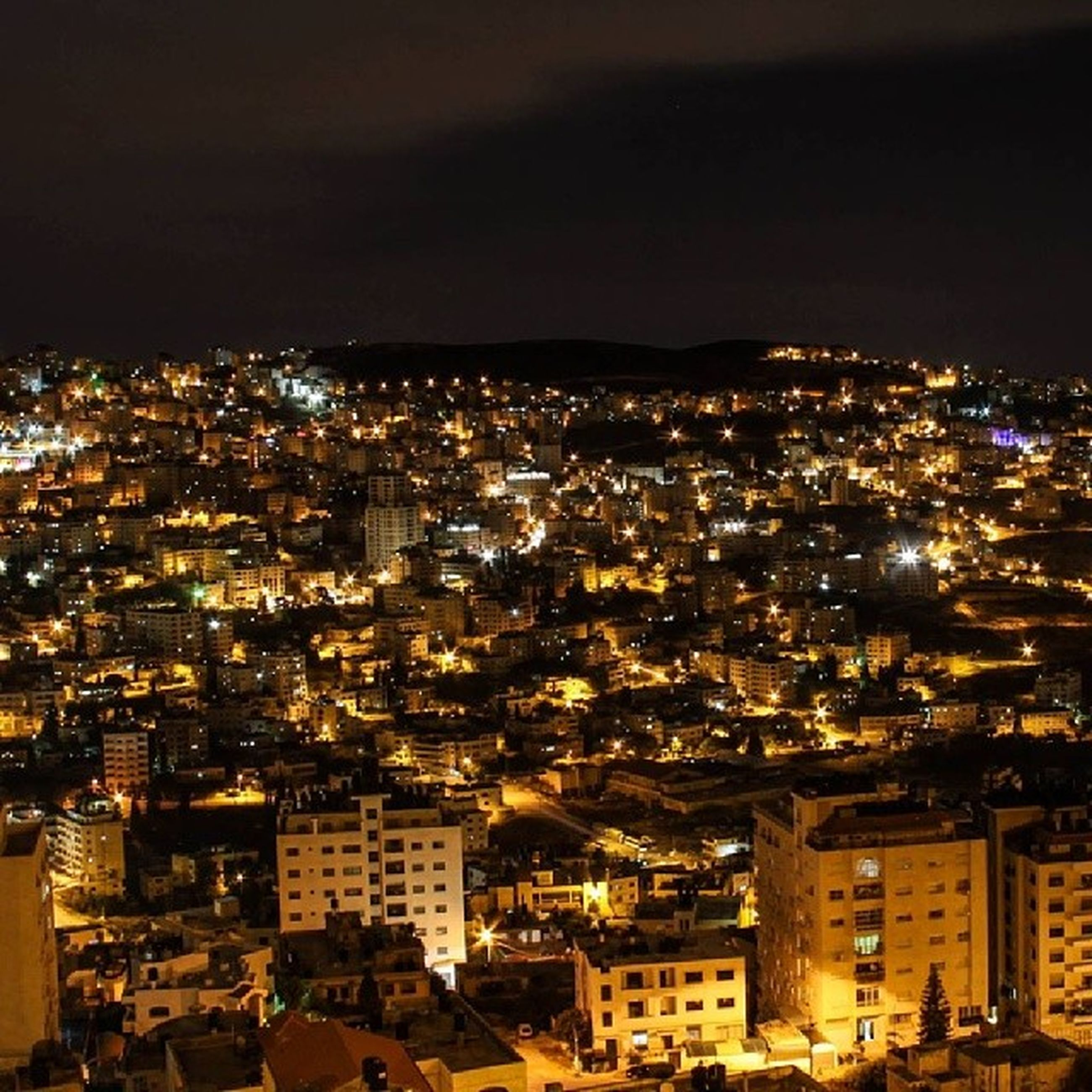 cityscape, illuminated, night, city, building exterior, architecture, crowded, built structure, high angle view, residential district, residential building, aerial view, residential structure, sky, city life, no people, community, outdoors, elevated view, copy space