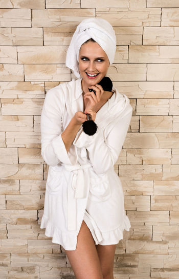 Happy Woman In Bathrobe Holding Make-Up Brush Against Wall