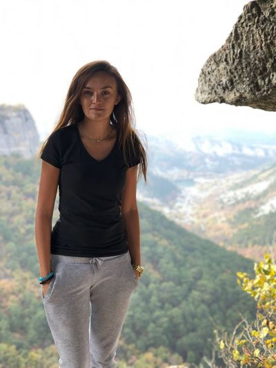 Portrait of smiling young woman standing on mountain against sky