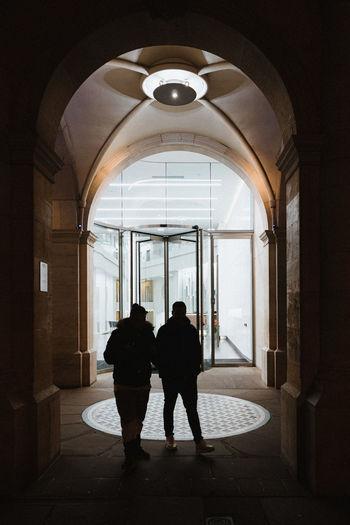 Rear view of silhouette people walking in corridor of building