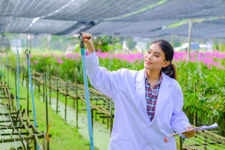 Woman holding umbrella standing in greenhouse