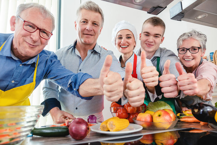 Portrait of smiling people showing thumbs up in kitchen